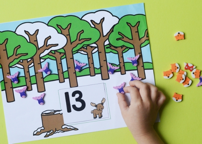 A child counting to 13 with the moose forest animal mini eraser counting activity mat.