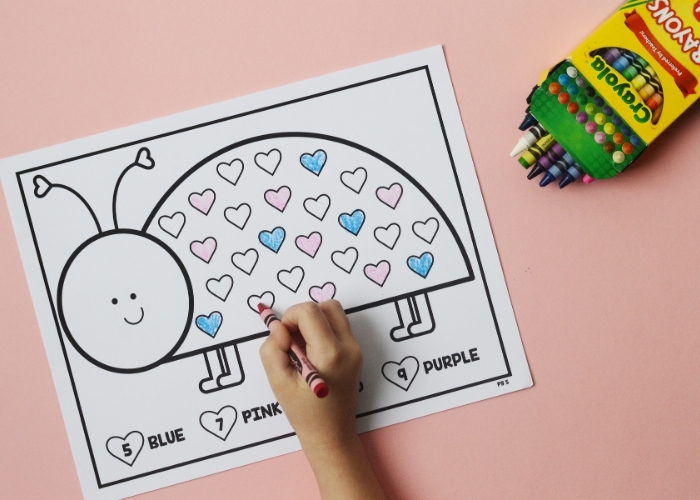 A child completing a lovebug numbers coloring sheet.