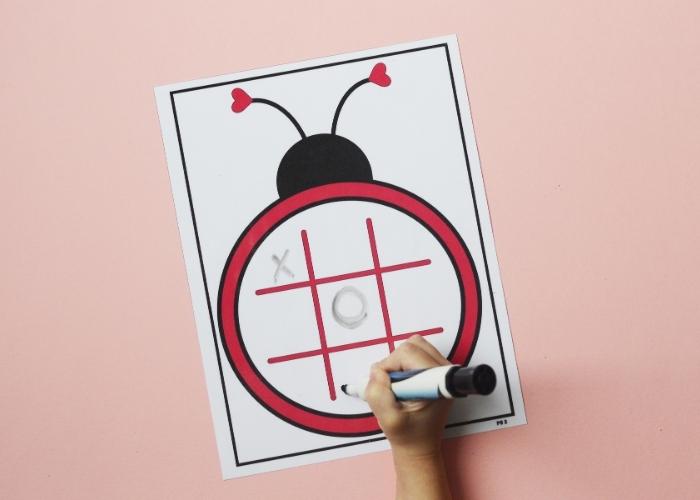 A child completing a ladybug tic tac toe lovebug activity worksheet.