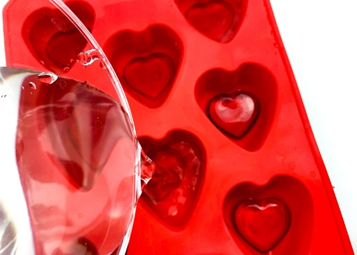 Pouring water into a heart shaped ice cube tray with red heart gems in them.