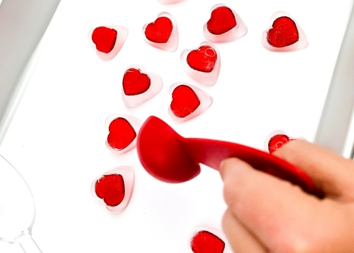 A kids using a red measuring cup to play with the preschool valentine's day sensory play with ice activity.