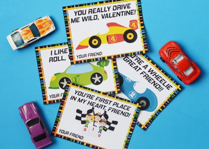 The Race Car Valentine's Day Cards printed and cut out surrounded by toy cars.