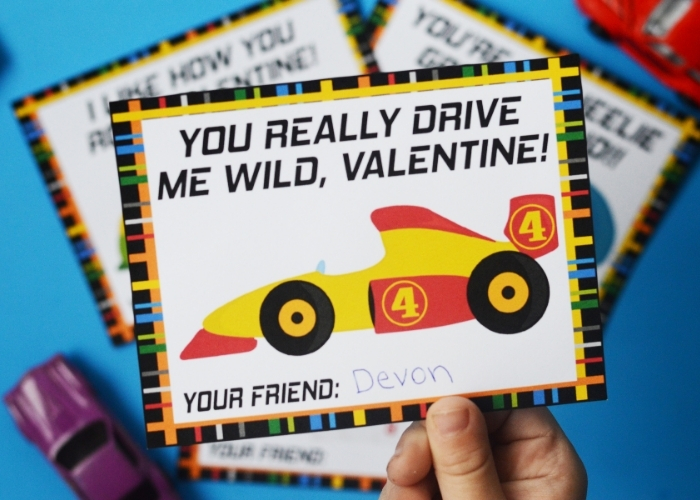 "A close up of a child holding a ""You really drive me wild, valentine!"" valentine's day card."