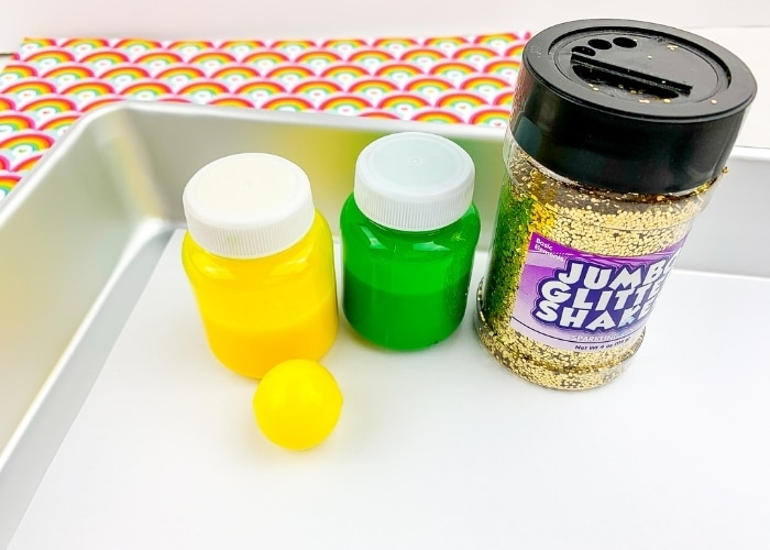 Yellow and Green tubs fo ginger paint with gold glitter and a yellow bouncy ball.