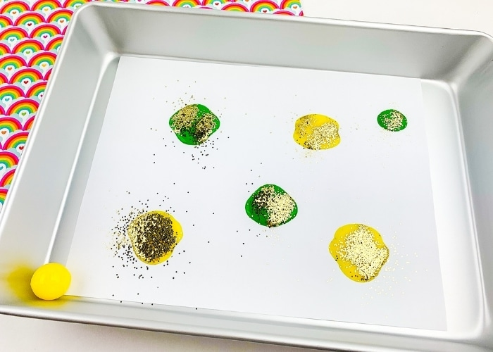 Yellow and green paint on a paper in a tray.