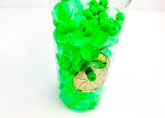 A close up of one of the finished St. Patrick's Day homemade sensory bottles.