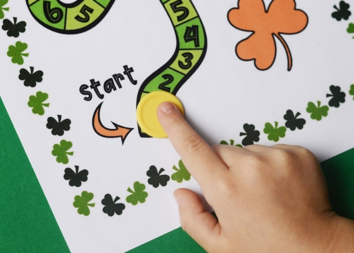 A child's hand moving the player token for the St Patrick's Day math activity board game.