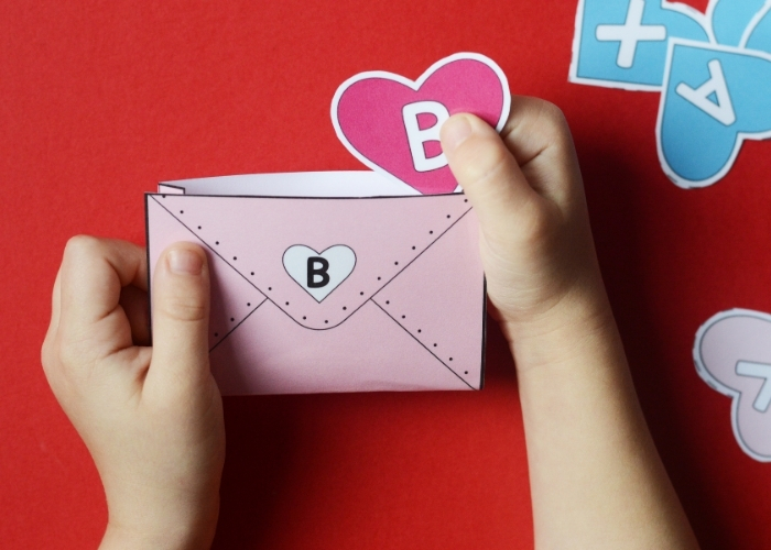 """A child placing a heart with the letter """"B"""" on it into the matching envelope for the valentines alphabet matching game."""