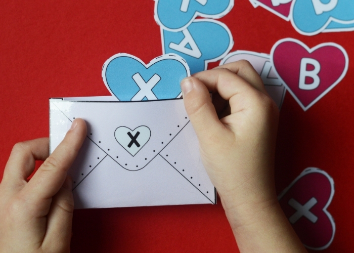 """A child placing an """"X"""" into an envelope with the same letter for the Valentine's alphabet matching activity."""