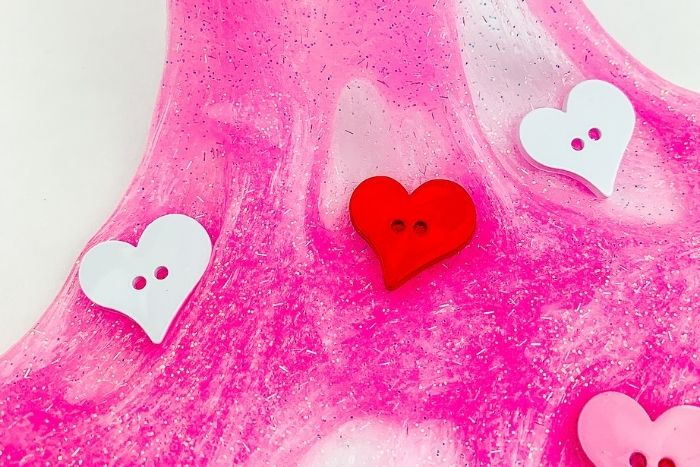 The finished Valentine's day slime with heart shaped buttons in it.