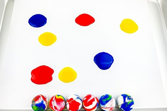 Spots of blue, yellow and red paint on a piece of paper with bouncy balls beneath them.