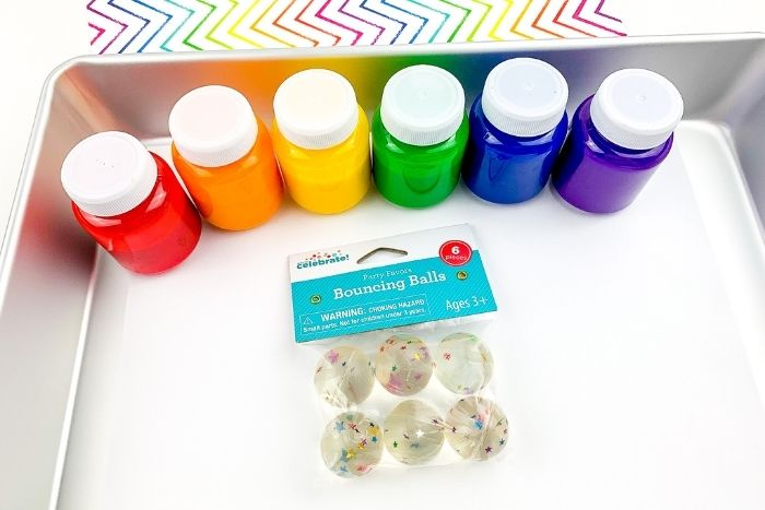 The supplies for the rainbow bouncy ball process art activity.