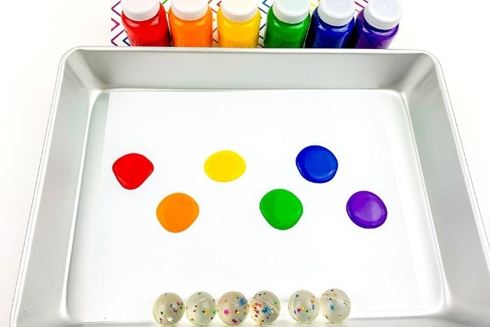 Spots of red, orange, yellow, green, blue and purple paint in a tray with bouncy balls beneath them.