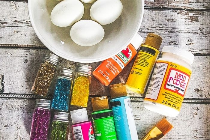 Supplies for making glitter Easter eggs.