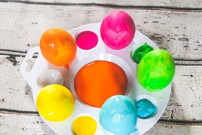 Easter eggs painted in bright colors on a paint tray.