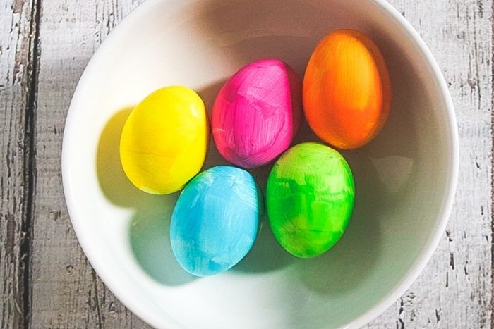 Easter eggs in a white bowl painted with bright colors.