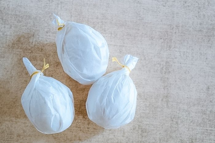 Eggs wrapped in white coffee filters secured with bread ties.