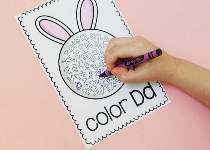 Child's hand coloring an Easter themed color the letter sheet with a purple crayon.