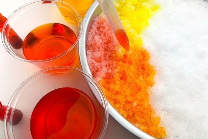 Overhead view of orange colored water being added to snow for the snow painting winter snow activities for preschool.