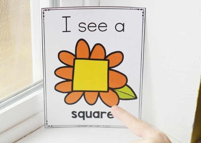 """A child pointing at a spring theme shape poster that says """"I see a square""""."""