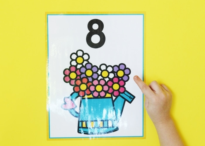 A child pointing at a spring theme number poster for the number 8.
