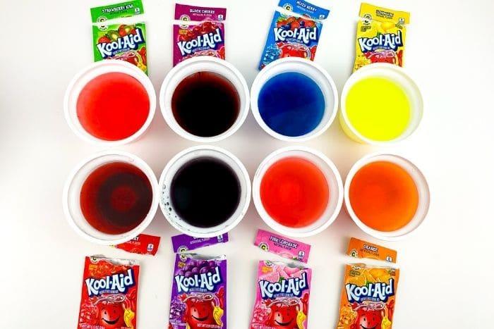 Cups of homemade egg dye using Kool-Aid.
