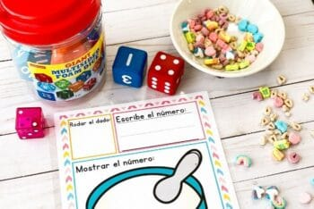 The supplies for the Marshmallow Cereal Roll and Count Math Game for Preschoolers in Spanish.