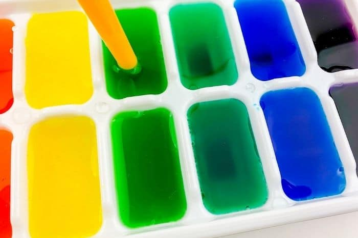 A close up of the food coloring being mixed into the water in an ice tray with a straw.