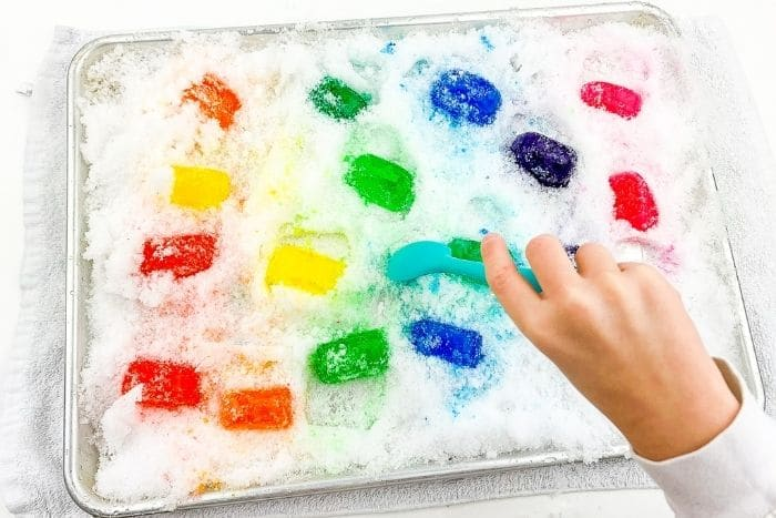 A child playing with the preschool snow and ice cube sensory bin.