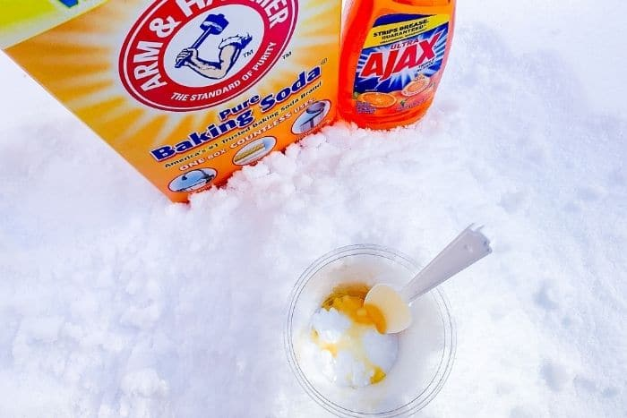 Overhead shot of dish soap and baking soda added to a cup in the snow.