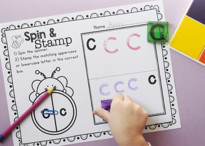 Overhead view of a child stamping a lowercase