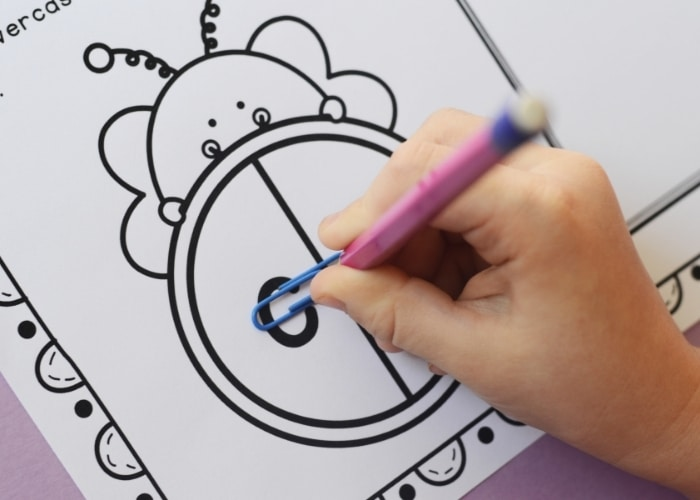 A child using the spinner on the Bee Theme Spin and Stamp Preschool Alphabet Worksheets.