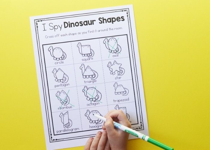 A close up of a child crossing off shapes on the