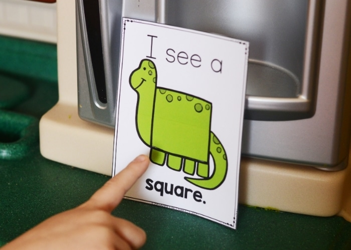 A child pointing at a Dinosaur 2D Shape Poster for the shape