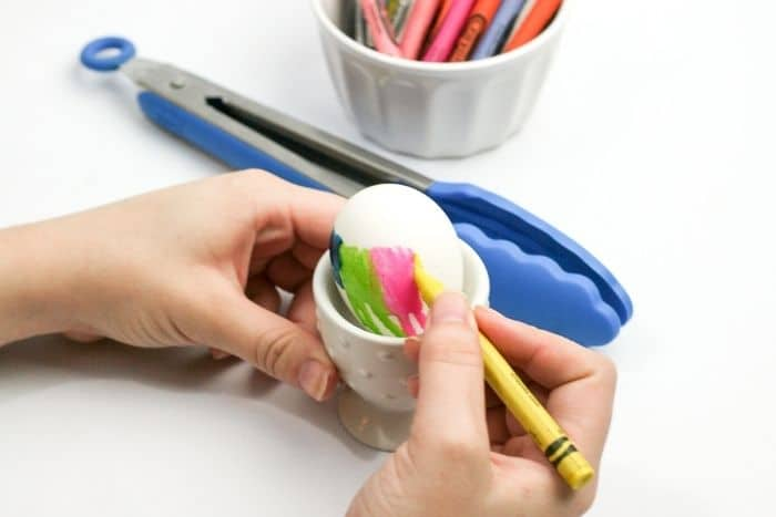 A child decorating an Easter egg by holding a crayon on a hot egg.