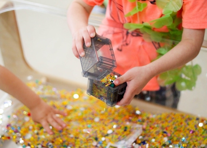 Close up of a child playing in the shimmery summer sensory bin.