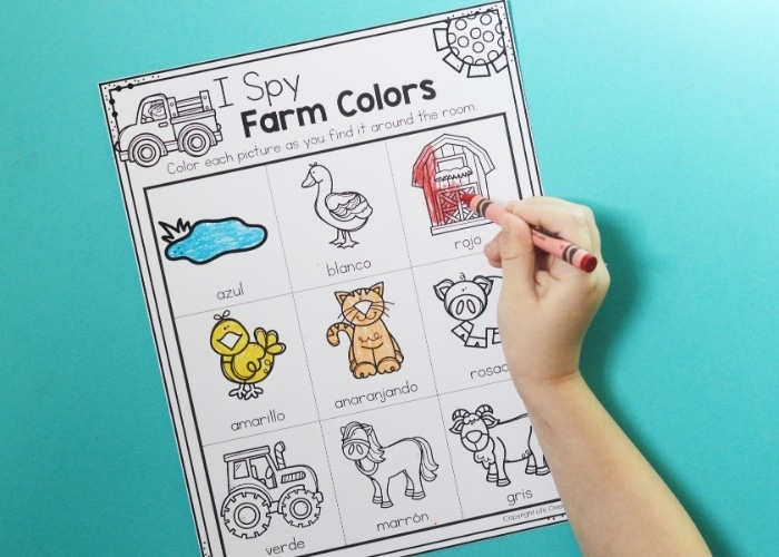 A child coloring a red barn on an