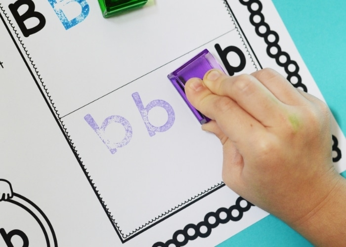 Child's hand stamping the letter B on a worksheet