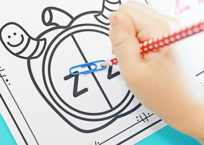 A child using a pencil and a paper clip as a spinner for the Apple Theme Alphabet Stamp Activities for Preschool.