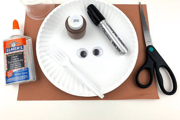 The supplies for the easy brown bear paper plate craft.
