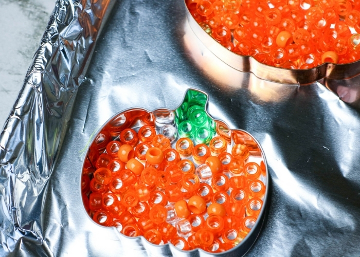 Overhead view of orange and green beads in pumpkin shaped metal cookie cutters.