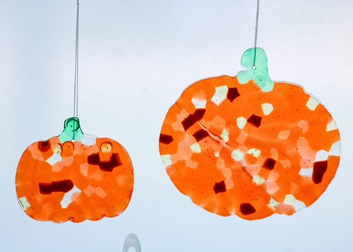 The finished Easy Melted Bead Suncatcher Pumpkin Craft for Kids hanging in a window.