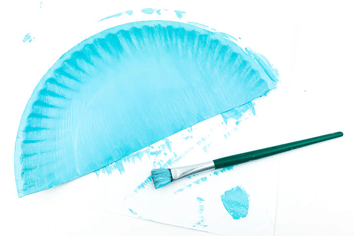 Half a plate painted for the ocean themed paper plate craft for kids.